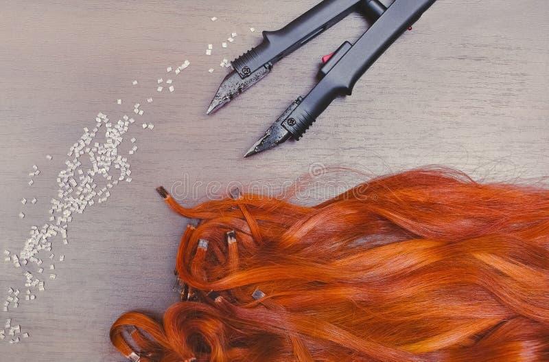 Capsules pré collées de kératine des prolongements rouges de cheveux, près des capsules de kératine et du fer d'extension de chev photo stock