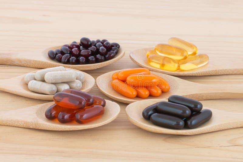 Capsules saines d'upplement de vitamine dans cuillères photo stock