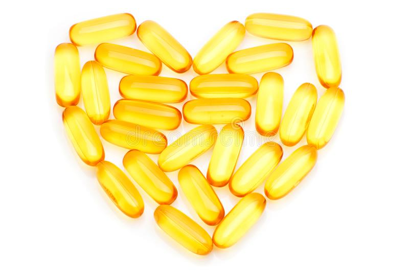 Capsules van het de olie de Omega 3 gel van de kabeljauwlever in de vorm van hart op wit stock foto's