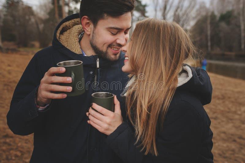 A captação do estilo de vida dos pares felizes que bebem o chá quente exterior em acolhedor aquece a caminhada imagens de stock royalty free