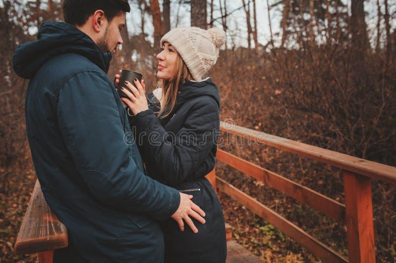 A captação do estilo de vida dos pares felizes que bebem o chá quente exterior em acolhedor aquece a caminhada imagens de stock