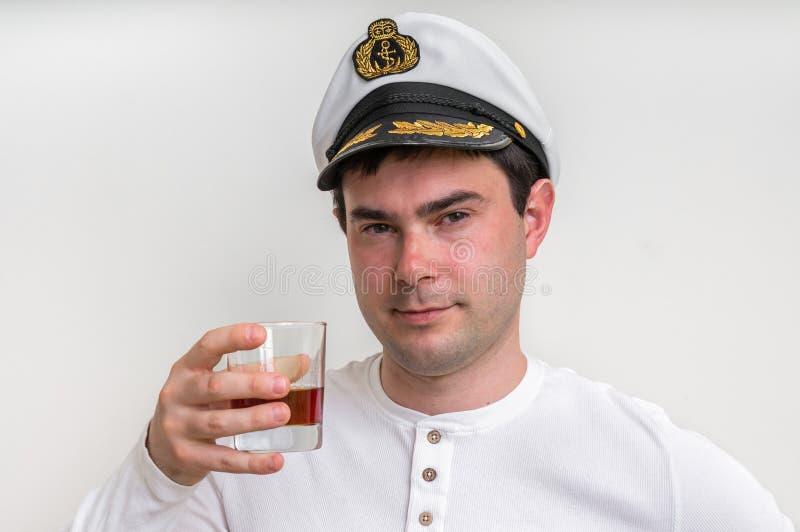 Captain com o tampão de marinheiro que guarda o vidro do uísque foto de stock