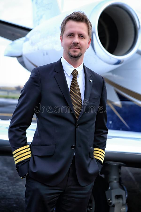 Captain by the jet. Pilot in command standing by the small jet plane royalty free stock image