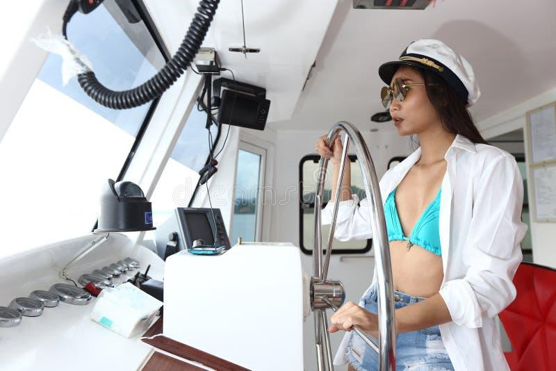 Captain a Lady en buey de la nave del control del bikini y del sombrero en el Ro de la función imagen de archivo libre de regalías