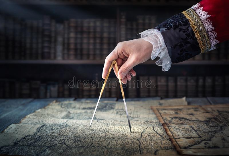 The captain of the old ship paves the course with the help of vintage maps and nautical divider. Old discovery, explorer, history. Pirates, travel, geography royalty free stock images