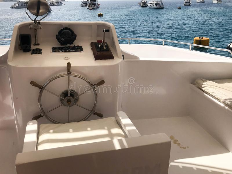 Captain`s cabin on a ship, boat, cruise liner with a steering wheel, dashboard with a sea compass and instruments for control aga stock photo