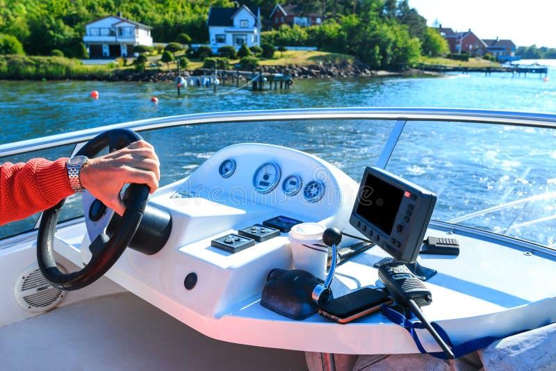 Captain's hand on steering wheel of motor boat royalty free stock photo