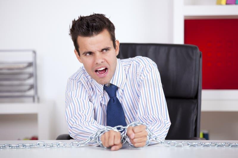 Captif d'homme d'affaires à son bureau photographie stock libre de droits
