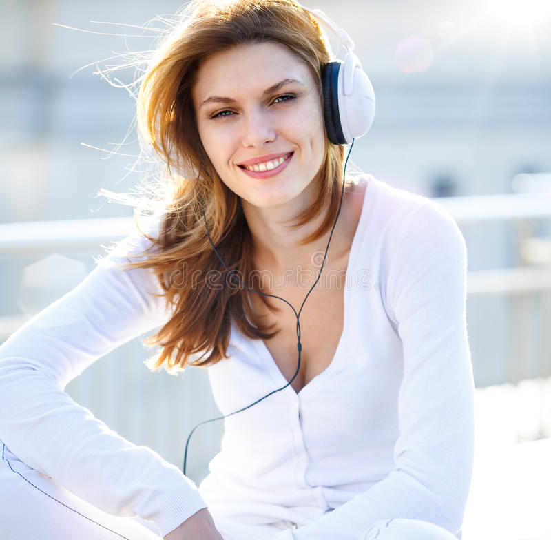 Captivating young woman listens to music through headphones. Smiling brunette girl in white clothes with white headphones looking at you royalty free stock photography