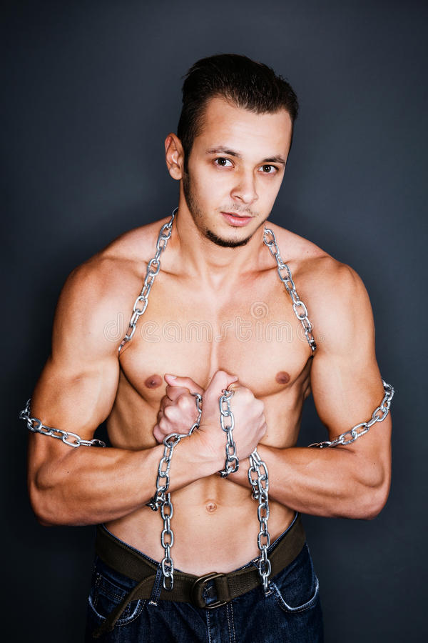 Captive in chains. Muscular man being captive in steel chains royalty free stock image