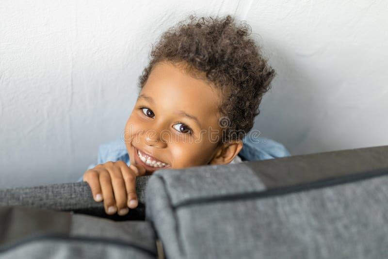 Captura de aproximação de um adorável sorriso afro escondido fotos de stock royalty free