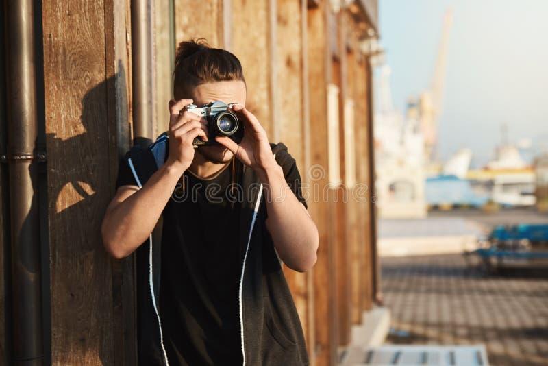 Captura de cada momento de vida Tiro al aire libre del fotógrafo elegante joven que mira a través de cámara del vintage, tomando  imagen de archivo libre de regalías
