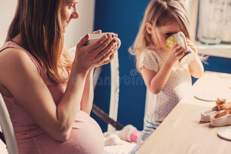 Captura de la forma de vida de la madre embarazada y del bebé que desayunan y que beben té en casa fotos de archivo