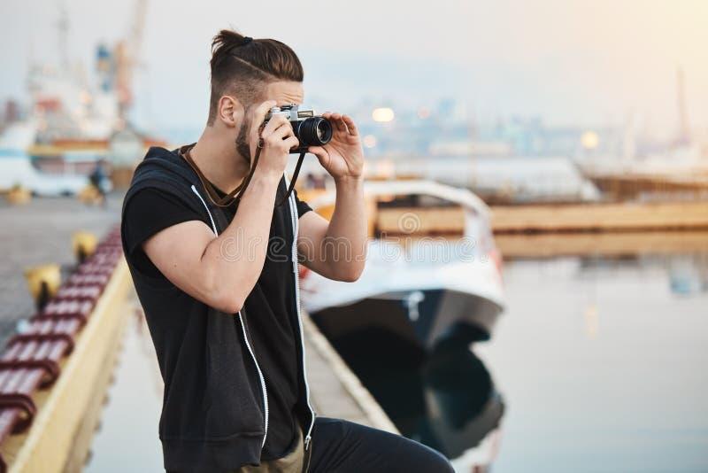 Captura de puesta del sol hermosa Fotógrafo europeo creativo soñador en el equipo elegante que se coloca en el puerto, tomando la imagen de archivo libre de regalías