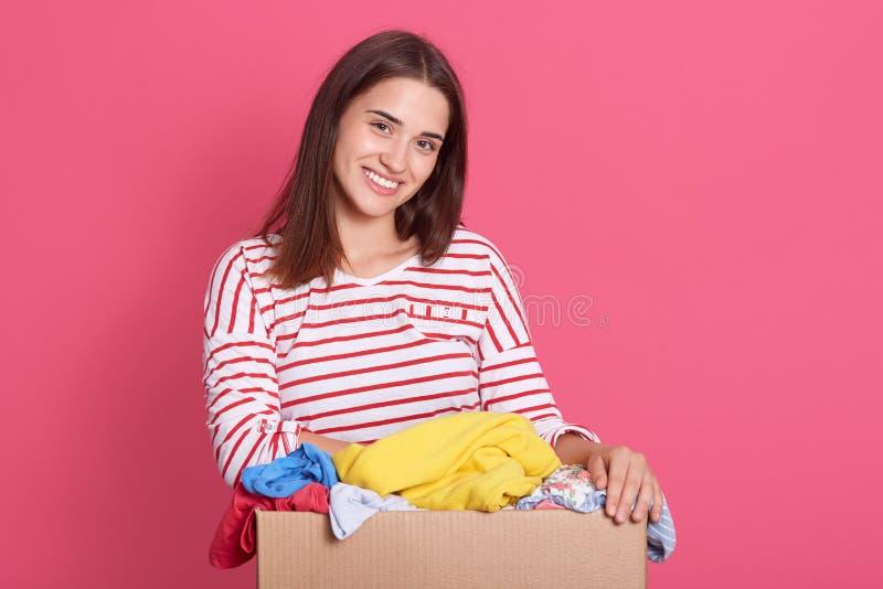 Captura horizontal de uma mulher morena sorridente vestida camisa casual listrada, olhando diretamente para uma câmara de ar com  imagem de stock