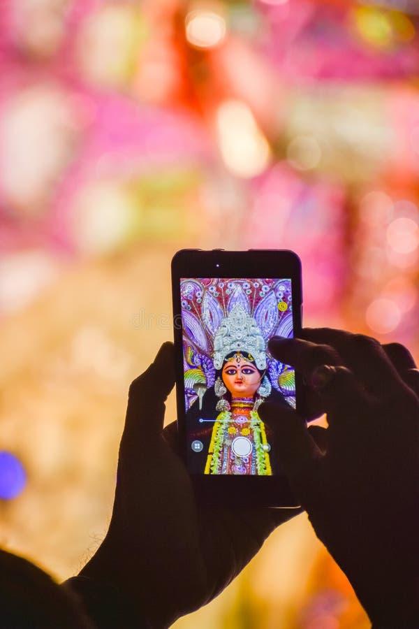 Capturando a fotografia de Durga Idol com telefone celular durante o festival do puja do durga imagem de stock royalty free
