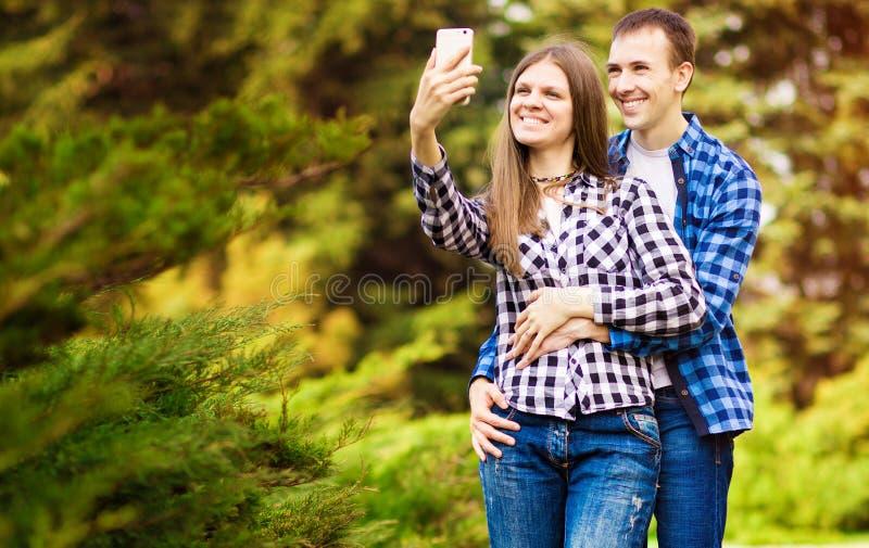 Capturando momentos brilhantes Pares de amor novos alegres que fazem o selfie na c?mera fotos de stock