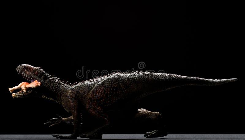 Capturas del juguete del Carcharodontosaurus un cierre más pequeño del dinosaurio para arriba en fondo oscuro fotografía de archivo libre de regalías