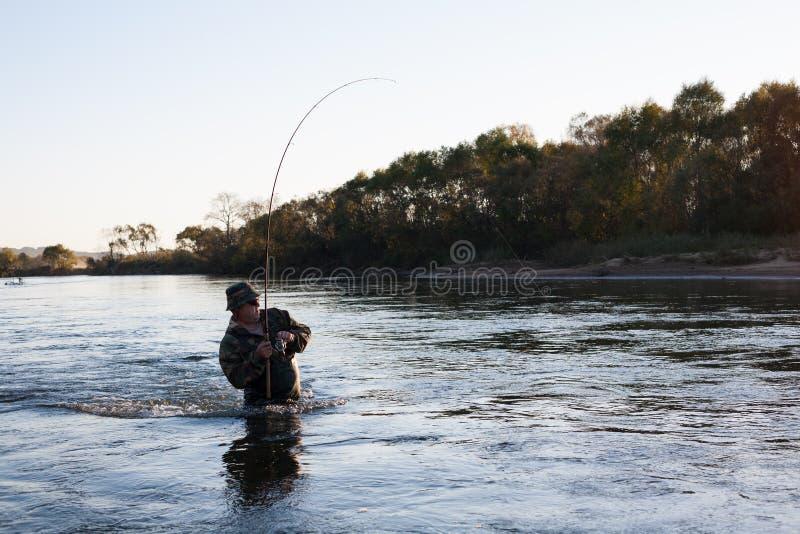 Capturas del pescador de salmones en la puesta del sol. fotos de archivo