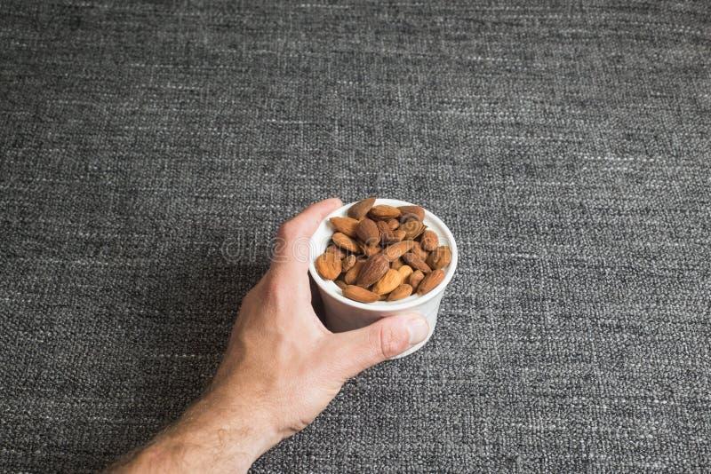Capture d'un bol blanc d'amandes épluchées sur la texture grise de tissu, l'espace de copie photo libre de droits