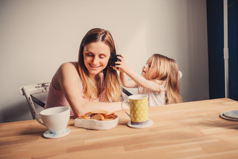 Capture de mode de vie de mère heureuse et de bébé prenant le petit déjeuner à la maison image stock