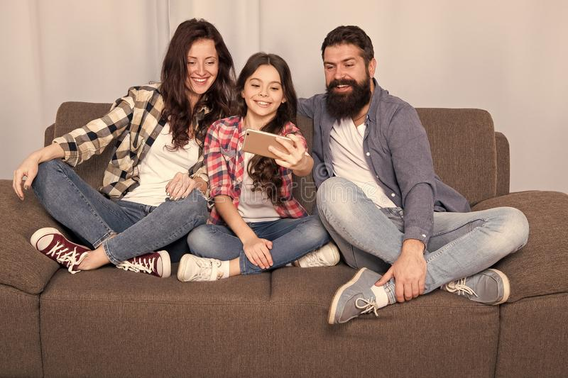 Capture happy moments. Family spend weekend together. Use smartphone for selfie. Friendly family having fun together. Mom dad and daughter relaxing on couch stock photography