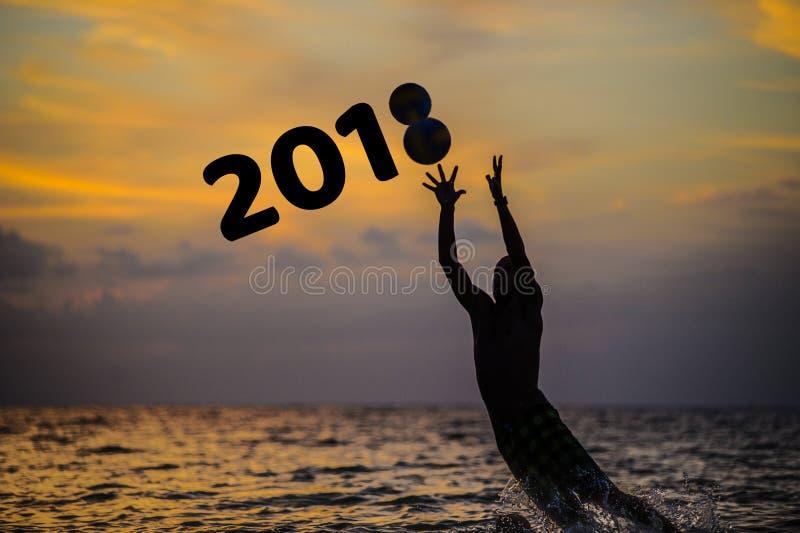 Capture la de la nouvelle année 2018 Silhouette de sauter d'homme de l'eau de mer photographie stock