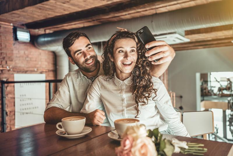 Capture moments!. Beautiful couple making selfie on new smartphone. Couple in love spends time in cafe stock photo