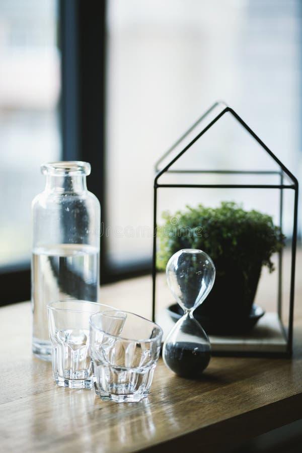 Capture sélective d'un verre à l'heure, pot de fleurs dans un verre en forme de maison et verres à boire photo stock