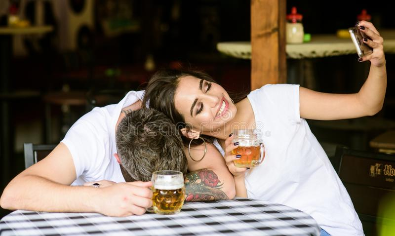 Capture shameful moment. Woman making fun of drunk friend. Girl taking selfie photo with drunk boyfriend. He appears too stock images