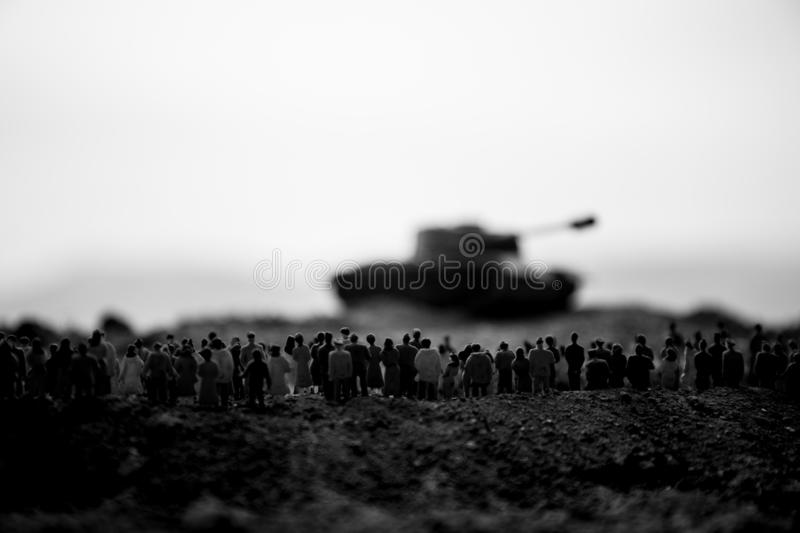 Captured by enemy concept. Military silhouettes and crowd on war fog sky background. World War Soldiers and armored vehicles. Movement while scared people royalty free stock image