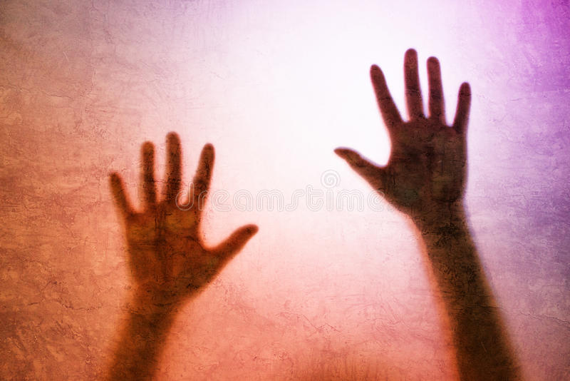 Captured person, back lit silhouette of hands behind matte glass. Captured female person concept with back lit silhouette of hands behind matte glass, useful as royalty free stock photography