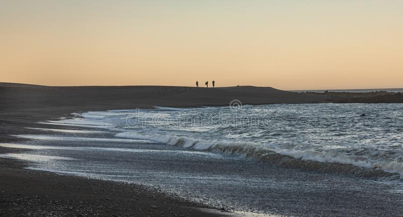 Hikers silhouette on Northern California Lost Coast of the King range at sunrise. Captured three silhouetted hikers with morning sunrise background with waves royalty free stock photography
