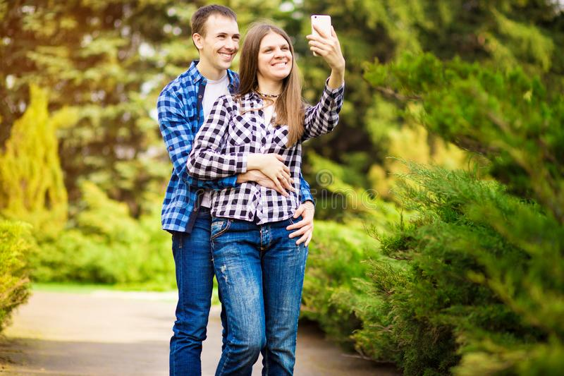 Capturing bright moments. Joyful young loving couple making selfie on camera. While standing outdoors stock photography