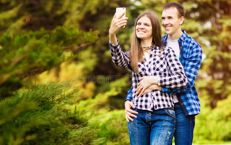 Capturing bright moments. Joyful young loving couple making selfie on camera. While standing outdoors stock photos