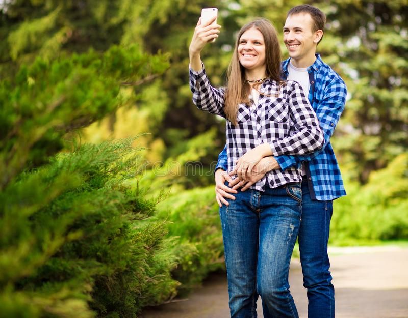 Capturing bright moments. Joyful young loving couple making selfie on camera. While standing outdoors royalty free stock images