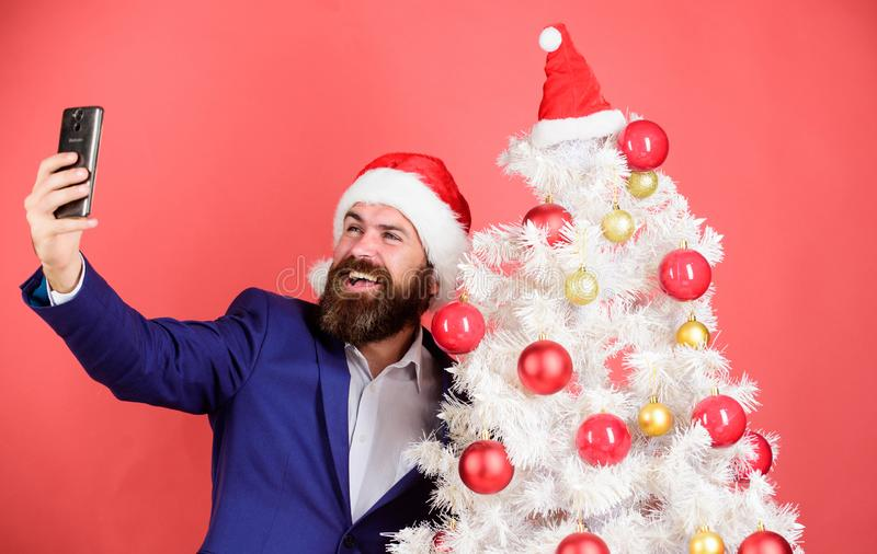 Capturing christmas memories. Man with beard and happy face send christmas greetings. Winter holidays concept. Santa. Claus takes selfie near christmas tree on stock image