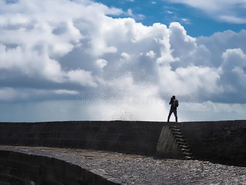 Capturing The Elements. A photographer, silhouetted against the stormy light, capturing the high waves and storm clouds at the Cobb harbour royalty free stock photography