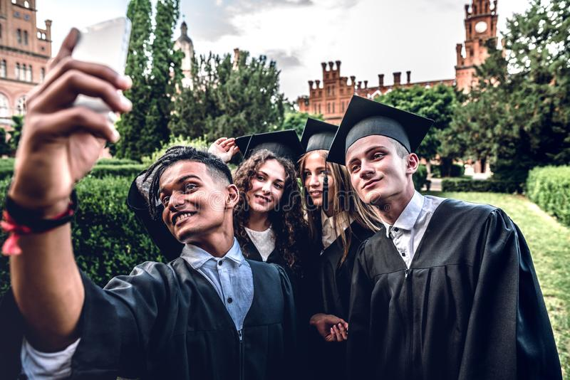 Capturing a happy moment.Making photo of graduates in mantles standing near university and smiling.  royalty free stock image