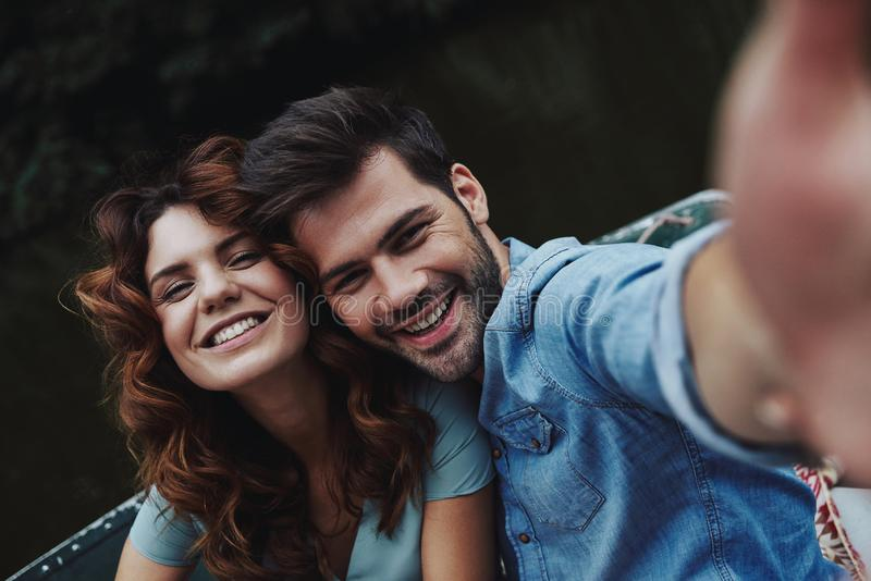Capturing happy moments. Self portrait of beautiful young couple looking at camera while sitting in the boat outdoors stock photo