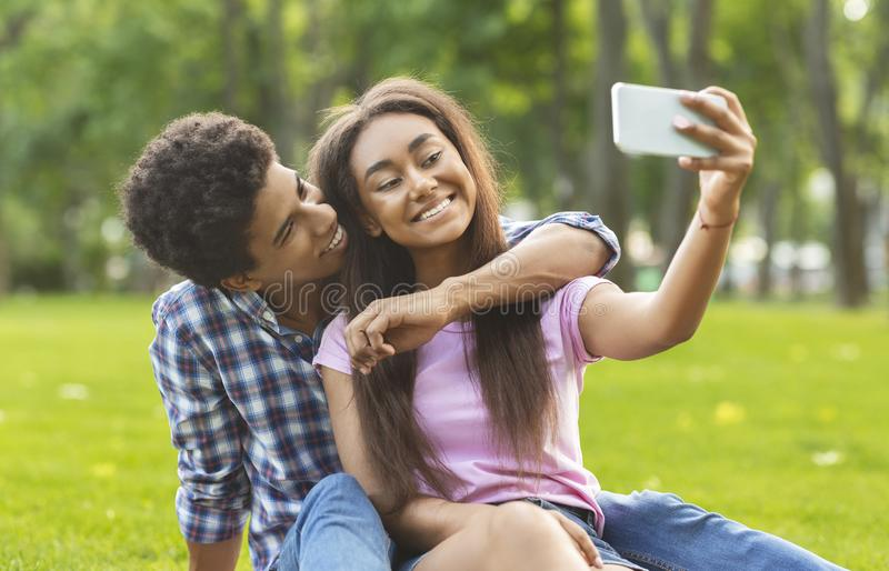 Capturing happy moments. Two cheerful teenagers making selfie outdoors royalty free stock photos