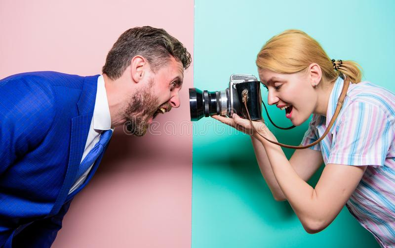 Capturing his face expression. Pretty woman using professional camera. Photographer shooting male model in studio royalty free stock images