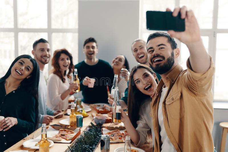 Capturing the moment. Group of young people in casual wear taking selfie and smiling while having a dinner party indoors stock images