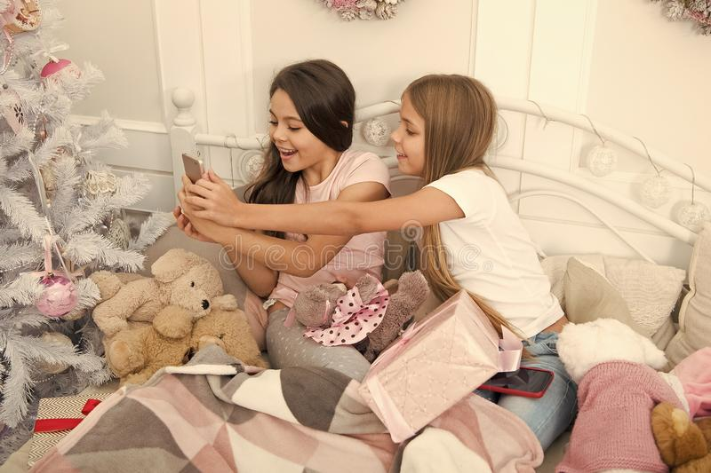 Capturing the moment. Small girls use smartphone in bed. Texting Christmas and New Year greetings by phone. Merry stock photo