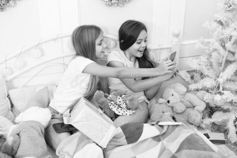 Capturing the moment. Small girls use smartphone in bed. Texting Christmas and New Year greetings by phone. Merry stock images