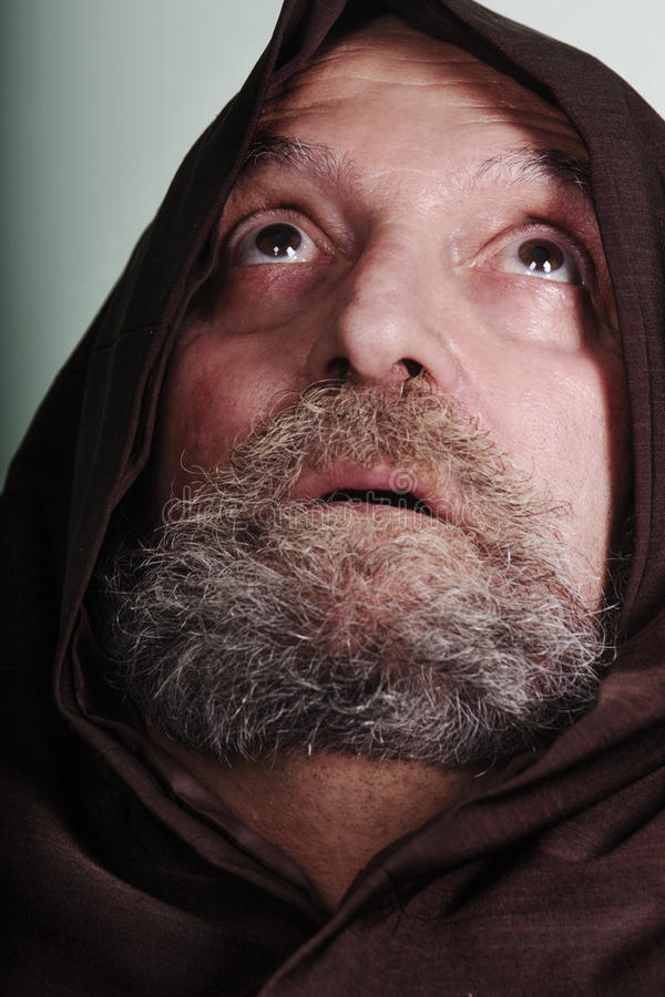 Capuchin monk with a beard illuminated by faith praying god. A monk with his robe looks up at the sky with eyes wide open. Concept of vocation to God royalty free stock photo