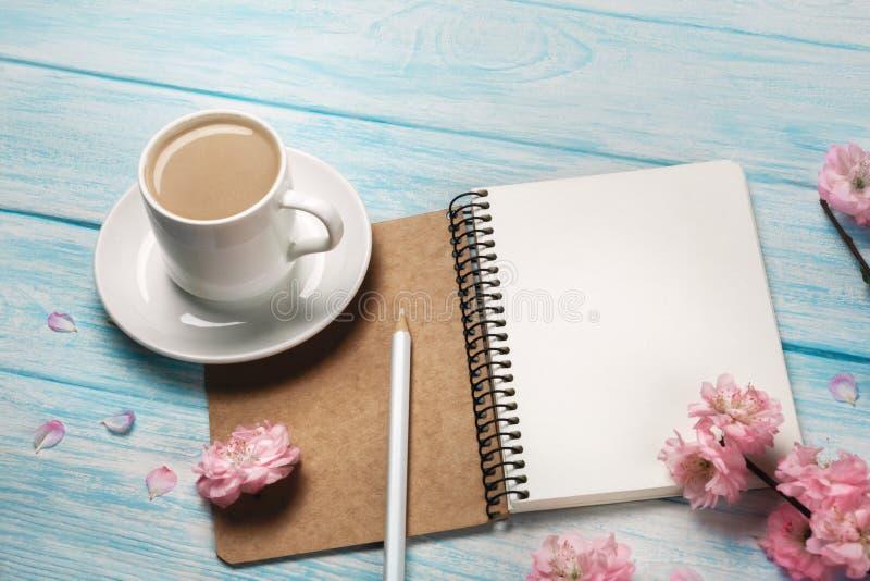 Capuchino blanco con las flores de Sakura, cuaderno de la taza en una tabla de madera azul fotos de archivo libres de regalías