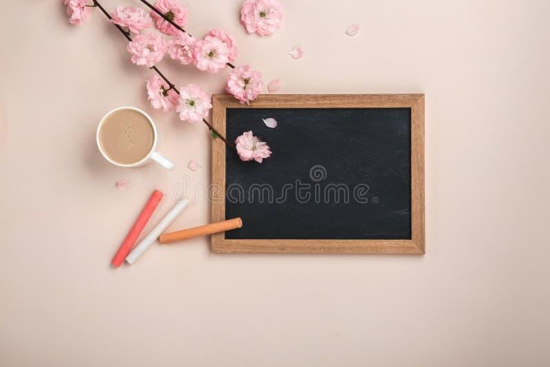 Capuchino blanco con las flores de Sakura, tablero de la taza de tiza en un fondo rosado en colores pastel imagen de archivo libre de regalías