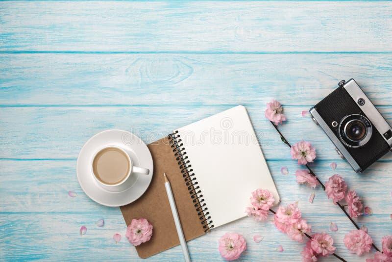 Capuchino blanco de la taza con las flores de Sakura, el cuaderno y la cámara vieja de la foto en una tabla de madera azul foto de archivo libre de regalías