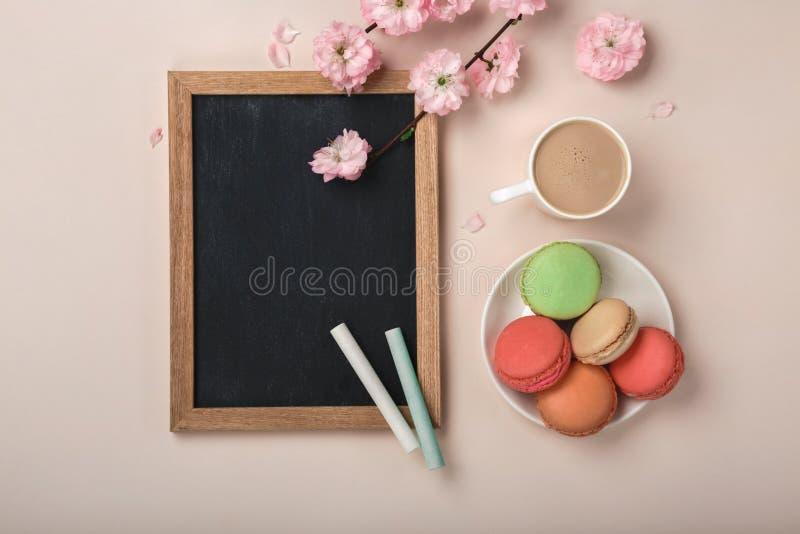 Capuchino blanco de la taza con las flores de Sakura, macarons, tablero de tiza en un fondo rosado en colores pastel fotografía de archivo